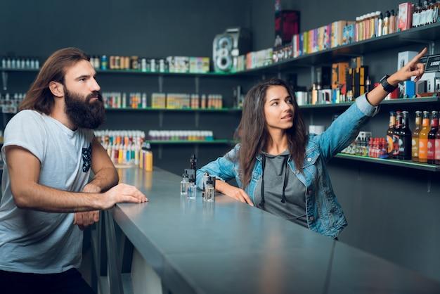 Mädchenverkäufer zeigt die wahl der elektronischen zigaretten.