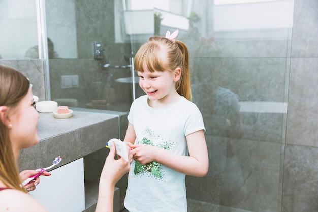Mädchenwarte-mutter, die zahnpasta auf bürste setzt
