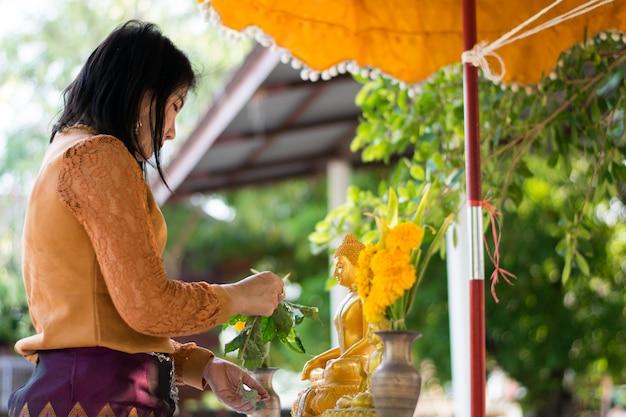Mädchenwasserbuddha im songkran festival