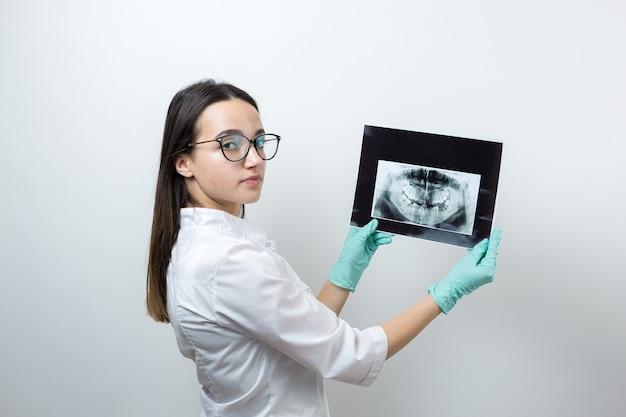 Mädchenzahnarzt in einem weißen kittel hält eine momentaufnahme der zähne des patienten.