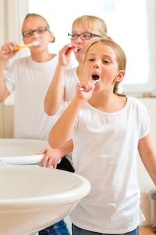 Mädchenzahnbürste im badezimmer