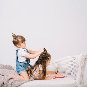 Mädchenzeichnung auf papier mit bleistift während ein anderes mädchen, das ihr haar einstellt
