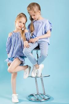 Mädchenzwillinge in der hellblauen kleidung werfen nahe einem barhocker auf.