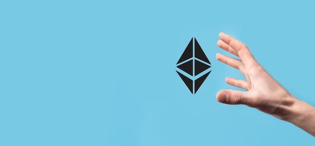 Männchen, das ein ethereum-symbol auf blauer oberfläche hält.
