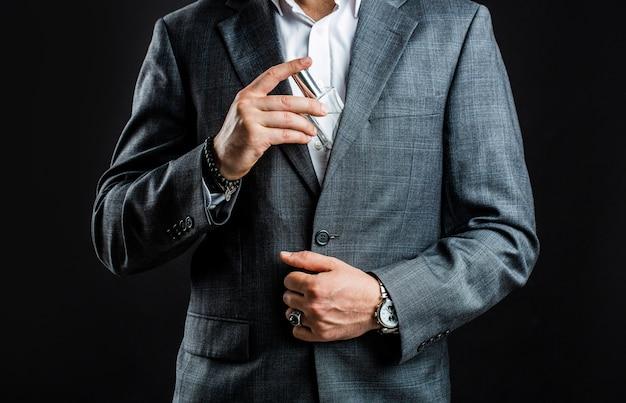 Männchen, das flaschenparfüm hält. mit armbanduhr in einem business-anzug abgeben.