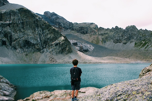 Männchen mit einem rucksack, der auf einer klippe steht und den blick auf das meer nahe einem berg genießt