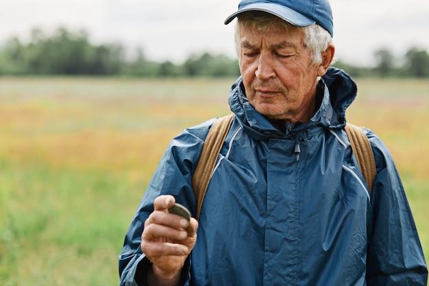Männchen mittleren alters mit blauer jacke, die alte münze auf der wiese hält,