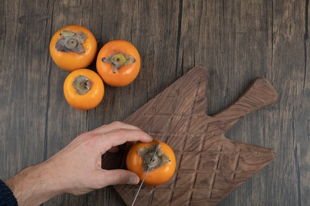 Männchen schneidet kakifrucht in zwei stücke auf holzoberfläche
