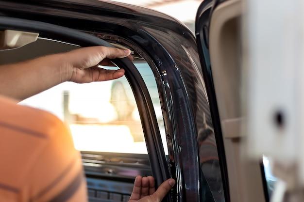 Männer benutzen ihre hände, um die schalldämmung im auto zu entfernen.