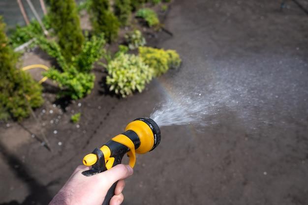 Männer bewässern den boden in einem garten im hinterhof ihres ferienhauses. bewässerung eines gemüsegartens an einem heißen sonnigen sommertag.