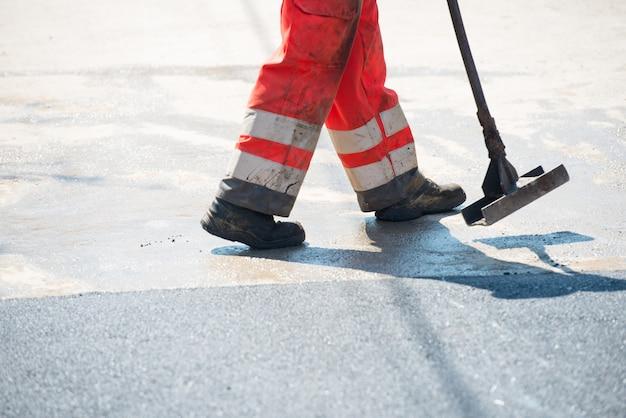 Männer, die an der neuen straße arbeiten, indem sie neuen asphalt setzen