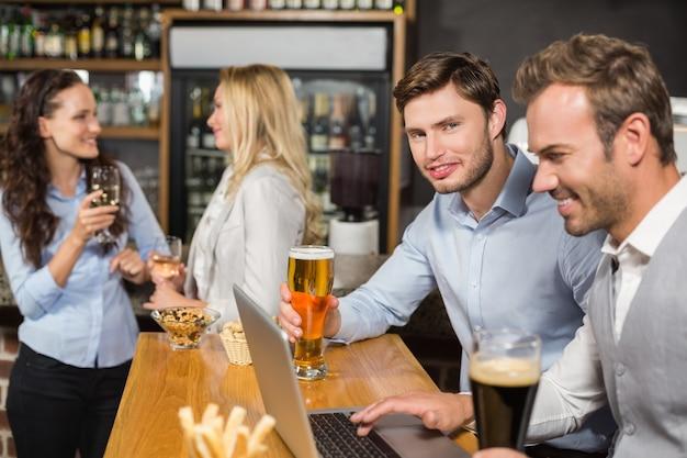 Männer, die an laptop arbeiten, während frauen hinten sprechen