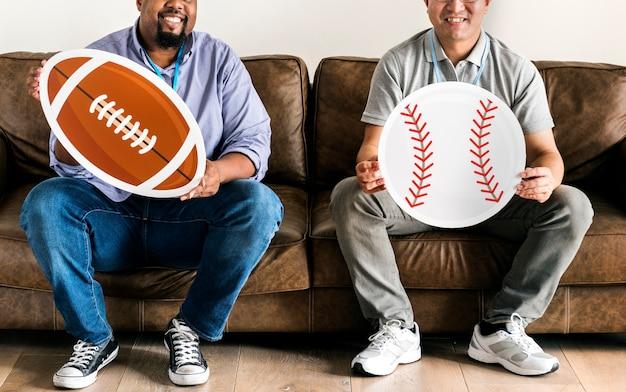 Männer, die baseball- und rugbikonen sitzen auf couch halten