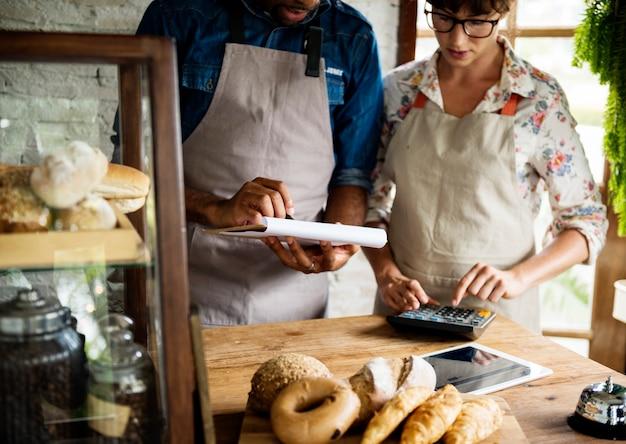 Männer, die den vorrat an gebäck in der bäckerei überprüfen