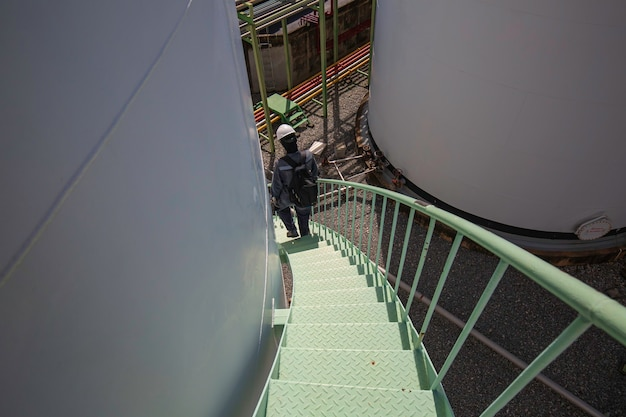 Männer, die die treppe hinuntergehen, inspektion visueller aufzeichnung des sicherheitsgurts des lagertanks bei hoher arbeit.