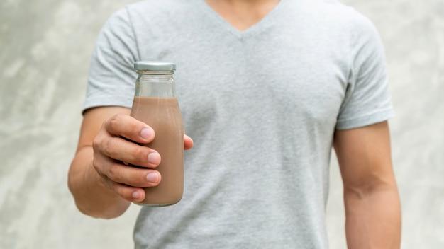 Männer, die eine flasche schokoladenmilch auf grauem hintergrund halten.