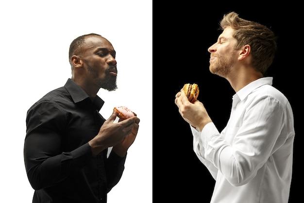 Männer, die einen hamburger und einen donut auf einem schwarzweiss-hintergrund essen. die glücklichen afro- und kaukasier. das burger, schnelles, ungesundes food-konzept