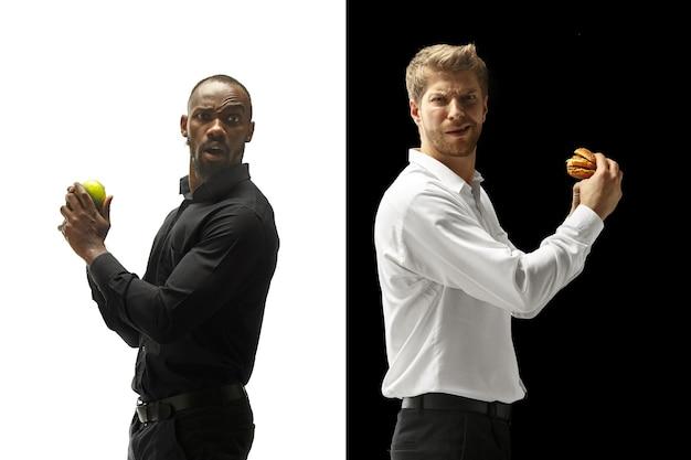 Männer, die einen hamburger und frische früchte auf einem schwarzweiss-hintergrund essen. die glücklichen afro- und kaukasier. das konzept für burger, schnelles, gesundes und ungesundes essen