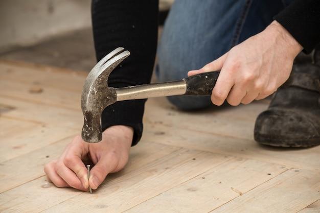 Männer, die einen hammer und einen nagel auf holz, erneuerungskonzept verwenden