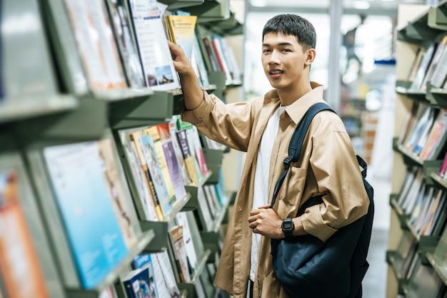 Männer, die einen rucksack tragen und in der bibliothek nach büchern suchen.