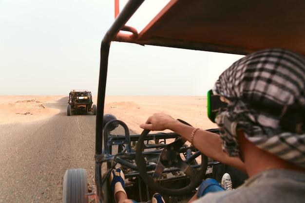 Männer, die fehlerhaftes auto in der wüste reiten