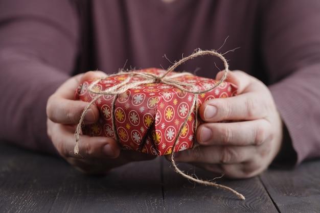 Männer, die handgemachte geschenkbox in den händen halten. weihnachtskonzept. neujahrsgeschenk