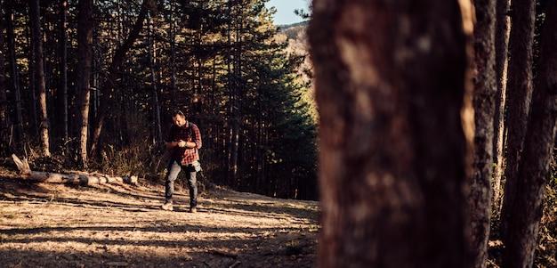 Männer, die intelligentes telefon im kiefernwald verwenden