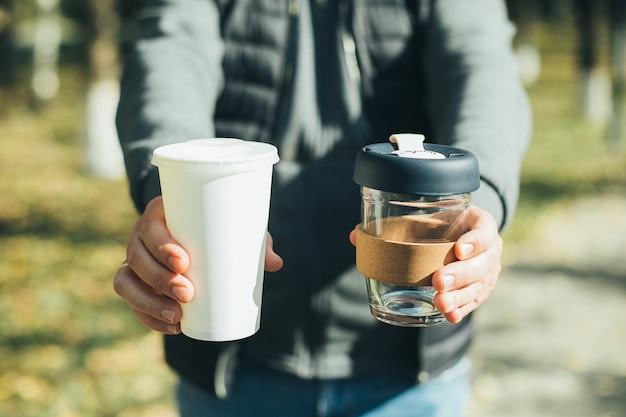 Männer, die kaffeetasse zum mitnehmen und einweg-pappbecher mit plastikdeckel halten. bewusste enscheidung. zero-waste-konzept