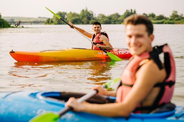 Männer, die mit seinem freund auf see kayak fahren