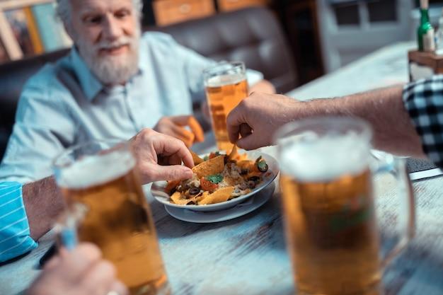 Männer, die nachos nehmen. nahaufnahme von alten grauhaarigen männern, die nachos nehmen, während sie bier trinken?
