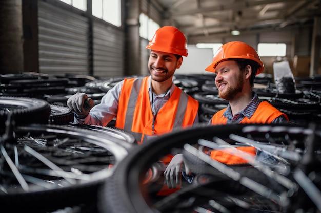 Männer, die neben ein paar rädern arbeiten