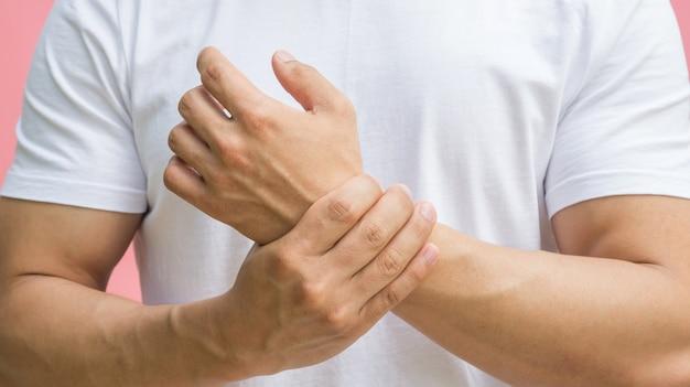 Männer, die schmerz in seinem handgelenk auf einem rosa hintergrund glauben.