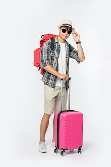 Männer, die zum reisen angezogen waren, brillen und hüte trugen, taschen und gepäck trugen