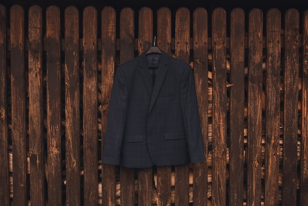 Männer dunkelblau braun schwarz formale klassische blazer hängen. brauner strukturierter holzhintergrund