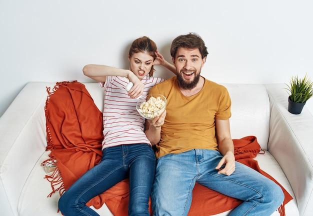 Männer frauen mit popcorn in einem teller drinnen auf dem sofa