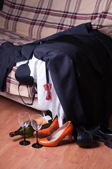 Männer-, frauenkleider und schuhe liegen nach der party auf der couch verstreut. eine leere weinflasche und gläser stehen auf dem boden