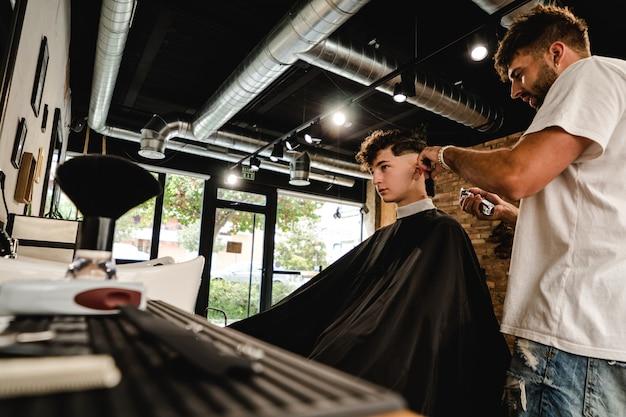 Männer-friseursalon. friseur, der haarschnitt im friseursalon tut.