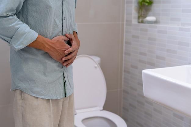 Männer haben bauchschmerzen, halten ihre hände am bauch und quälen das gesicht der toilette in der toilette.