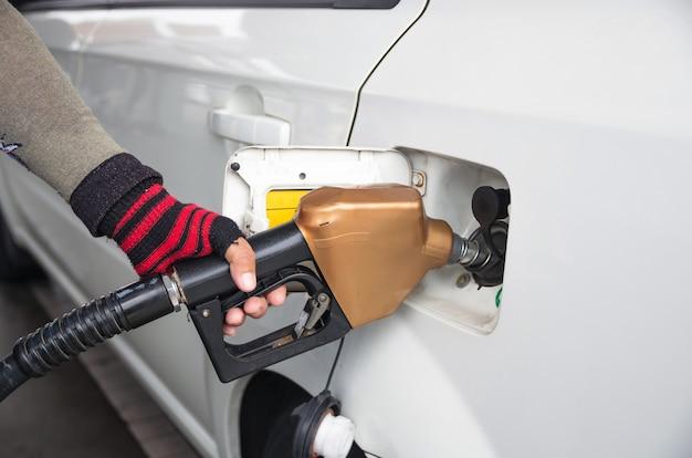 Männer halten kraftstoffdüse, um kraftstoff im auto an der tankstelle hinzuzufügen