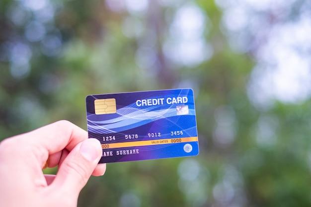 Männer halten kreditkarte auf bokeh natur
