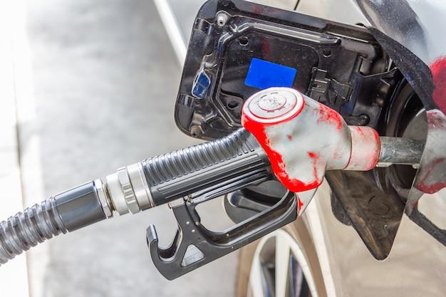 Männer halten zapfpistole, um brennstoff im auto an der tankstelle hinzuzufügen