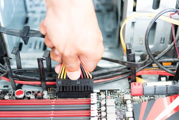 Männer handgriff verbinden netzstecker und kabel zum stromanschluss am motherbord im computer-atx-gehäuse