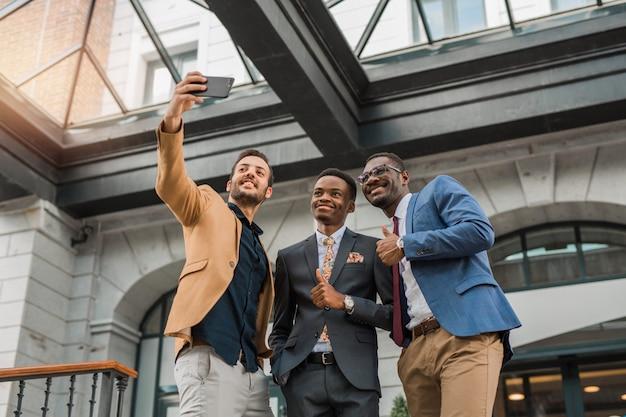 Männer in anzügen, die selfie machen