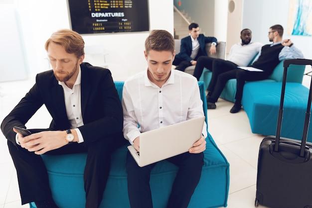 Männer in anzügen sitzen im wartezimmer am flughafen.