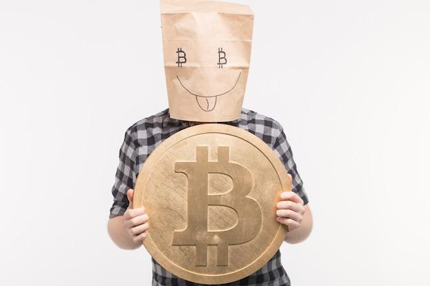 Männer in fröhlicher papiertütenmaske mit bitcoin an den händen.