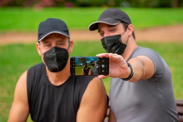 Männer in masken im park, die sport treiben und ein selfie mit einem smartphone machen