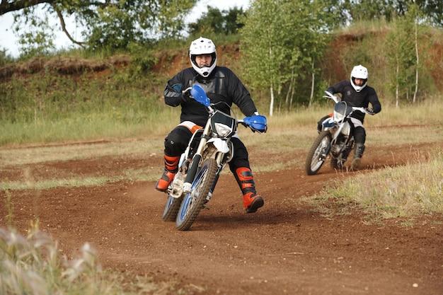 Männer in schutzkleidung genießen das motorradfahren auf schmutziger straße, während sie auf unebener strecke gegeneinander antreten