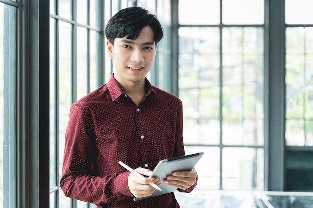 Männer lächeln und sind fröhlich. verwenden sie das tablet und halten sie es zur hand. er benutzt tablette, um zu arbeiten, c