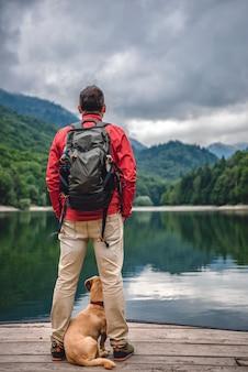 Männer mit einem hund stehen am pier am see