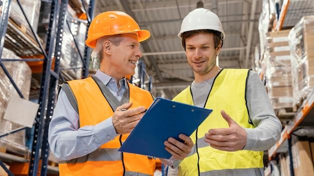 Männer mit helm arbeiten logistisch
